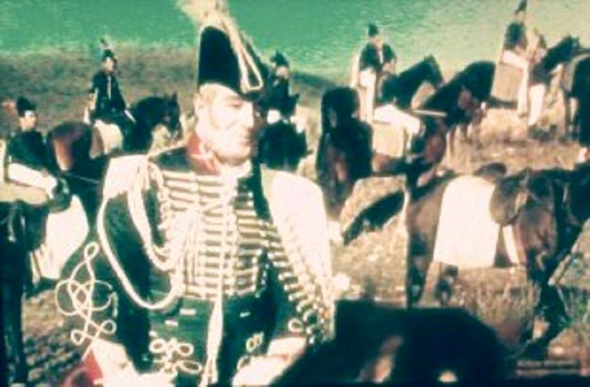 Vittorio de Sica sobre caballo de cartón piedra, rodeado de extras jimenatos.