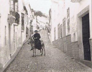 El cura Alegre subido a un burrito en c/ Sevilla de Jimena a la altura del entonces Cine Capitol, y no está para vigilar los pecados de su interior