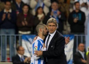 El enrenador de Málaga, Manuel Pellegrini, abrazado al Izco, al final del parido de fútbol con el Osasuna