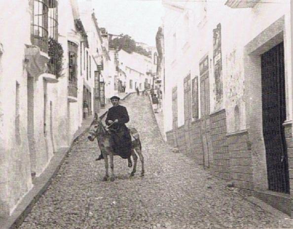 El cura Luis Alegre en borriquito a la altura de la fachada del cine Capitol en calle Sevilla