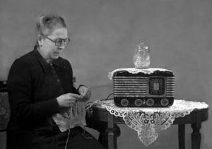 Mujer oyendo novela radiofónica a la vez que haciendo un jersey con ochos