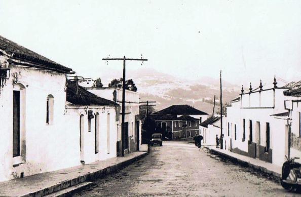A la inversa la perspectiva de la calle de entrada a la Estación. Aquí como salida hacia Jimena. Año 1963. Eso día llovía. La cortina de agua observando Jimena, hecho que era más frecuente que sucediera. Año 1963. Ediciones OBA.