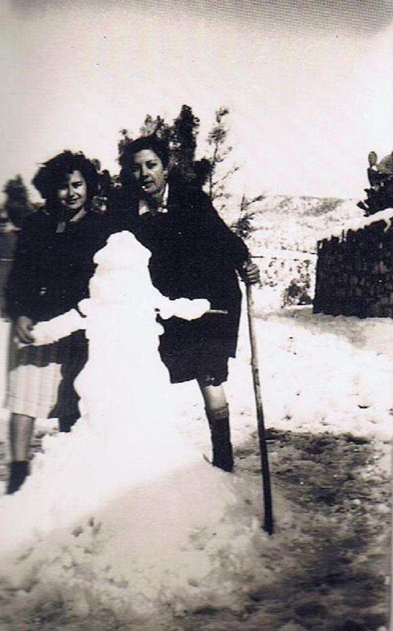 Anita Álvarez Quirós y Antonia Duarte Riquelme, junto al muñeco que han hecho con la nieve. Año 1954. Fuente Ediciones OBA.