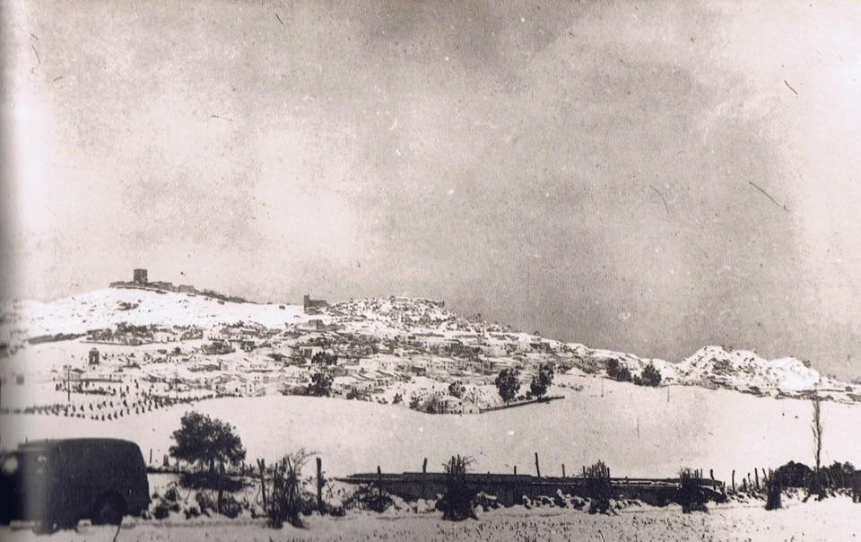 Amanecer en Jimena, mañana del 3 de febrero de 1954, tras haber estado nevando desde el atardecer del día anterior. Imagen tomada a pie de la carretera de la Estación de tren a San Pablo de Buceite, dentro de carretera, Algeciras-Ronda. Año 1954. Fuente: Ediciones OBA.