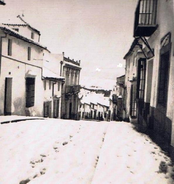 Nevada en la calle Sevilla en su bajada, tomada a la altura de lo que fue la escuela nacional del maestro don Antonio Puchán, hoy sede de la asociación ecologista . A mano izquierda con balcones la casa del médico, don Juan Marina, hoy hotel Rural. Año 1954 Ediciones OBA