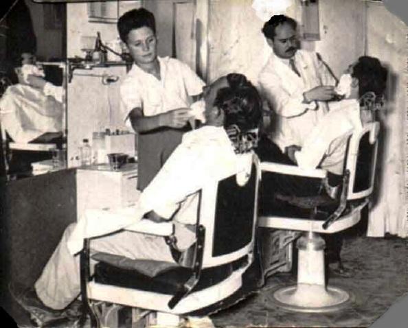 El aprendiz del maestro barbero enjabona al cliente para resblanceder la barba del cliente para que entre mejor la cuchilla del barbero a la vez que no la fina navaja del maestro. Fuente;