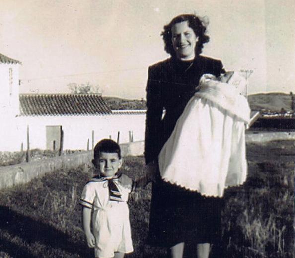 Año 1953. En el jardín. Marinero en tierra de la mano de mi madre, Isabel, de luto por la muerte de su padre, mi abuelo, Bartolomé, que sujeta en su brazo izquierdo a mi hermano, Miguel Ángel. Detrás, a mano izquierda la fábrica de harina de los Vallecillos y a mano derecha al fondo, la Estación. Foto propia.