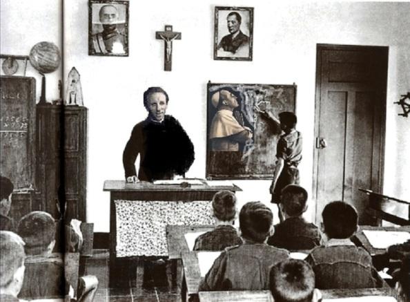 La Escuela Nacional. Sacerdote impartiendo la clase. Al fondo la efigie del Papa Pio XII entre Franco y Jose Antonio Primo de Rivera, fundador de la Falange Española, único partido político que la Dictadura tenia como legal. Fuente, Google.